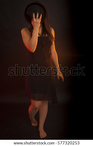 Woman dancing with a hat in front of the face