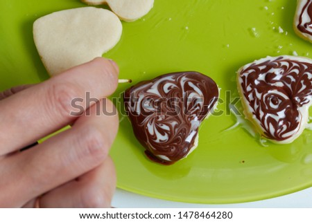 Woman decorates biscuit cookies with icing of white and black chocolate