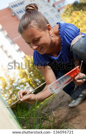 Woman decorates the walls of buildings #136096721