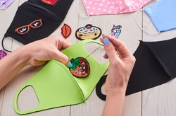 Woman decorating a green face mask with a strawberry sequin patch. Nice DIY restyle for a boring face accessorie.