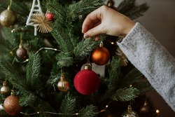 Woman decorating christmas tree with red bauble closeup. Preparation for christmas time. Modern simple ornament in hands on background of festive tree in lights. Happy holidays