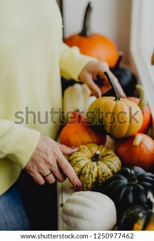 Woman decorating her house with pumpkins and squashes