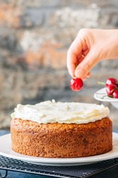 Woman decorating homemade cream cheese frosting sour cream cake with fresh and ripe cherries.