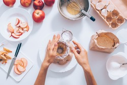Woman decorating seasonal autumn cake, flat lay composition. Female's hands holding sieve with powdered sugar over apple pie near ingredients and kitchenware, top view.
