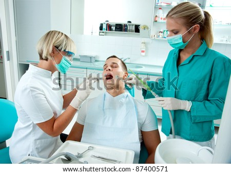 woman dentist and her assistant working on male patient