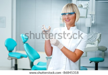 woman dentist holding dental model