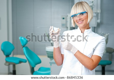 woman dentist holding dental model