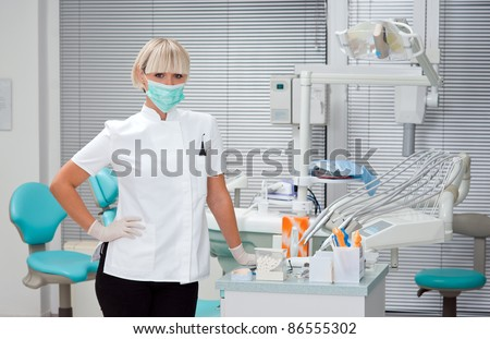 woman dentist standing in her office wearing mask