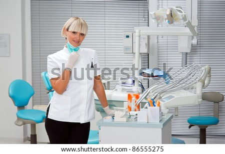 woman dentist standing in her office with mask