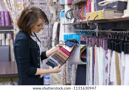 Woman designer, decorator chooses fabrics for curtains, pillows, embroidering fabrics, carpets in the textile show room Stok fotoğraf ©