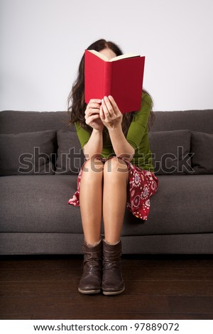 woman detail sitting on a brown sofa reading a book - stock photo