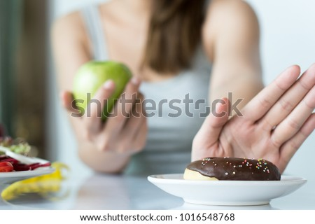 Woman dieting for good health concept. Close up female using hand push out her favourite donut and choose green apple and vegetables for good health.