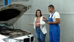 Woman discuss the motor of car with mechanic with tablet