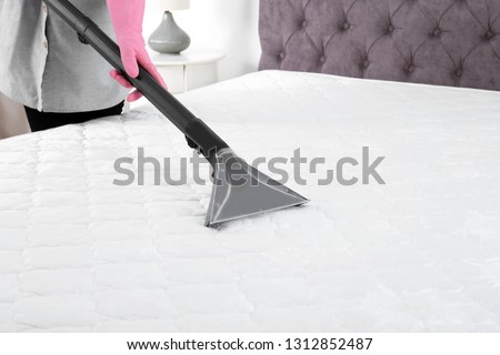 Woman disinfecting mattress with vacuum cleaner, closeup. Space for text