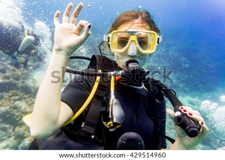 Woman diving in her vacation on coral reef giving the ok sign