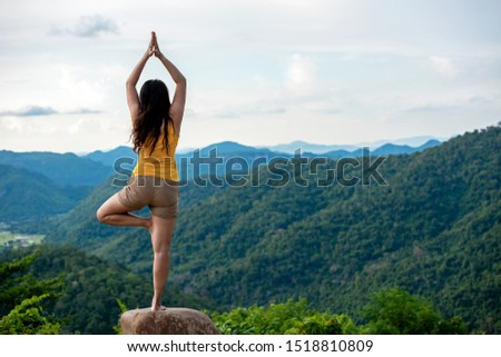 Woman do yoga lifestyle balance practicing and zen in outdoor. Woman exercising vital and meditation for fitness lifestyle club at the nature mountain background.   Healthy and Relax Concept