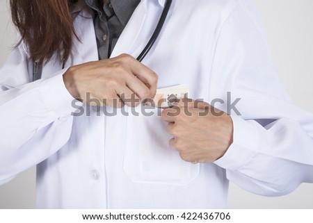 woman doctor hands with white gown and stethoscope tucking a wad of Euro banknotes in her pocket #422436706