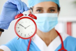 Woman doctor in protective medical mask holds an alarm clock. Medical accident insurance and coronavirus concept