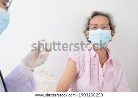 Woman doctor is preparing a vaccine for an older, gray-haired Asian woman wearing white shirts to build the coronavirus or COVID-19 immune system.