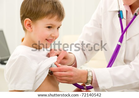 woman doctor listening to heartbeat of 4 years old boy in office