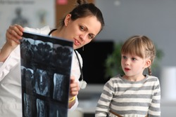 Woman doctor shows child patient an xray in clinic. Use of radiation diagnostics of diseases of skeletal system in pediatric practice concept.