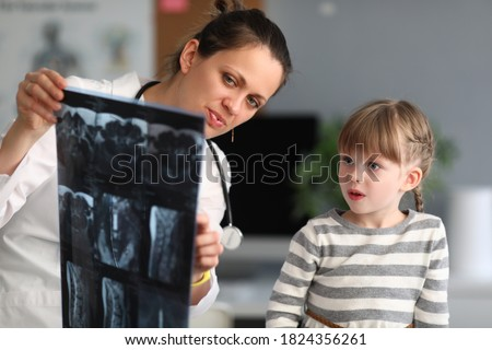Woman doctor shows child patient an xray in clinic. Use of radiation diagnostics of diseases of skeletal system in pediatric practice concept. Foto stock ©
