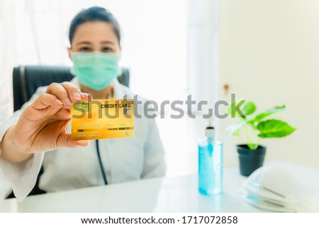 Woman doctor wearing uniform with hygiene mask and stethoscope sitting at desk holding credit card with sanitizer or alcohol gel and N-95 mask, plant pot on white table in office room at hospital. Stock foto ©