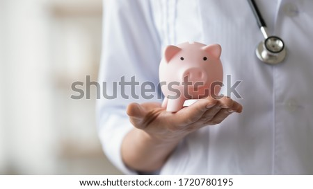 Woman doctor wearing white coat and stethoscope holding piggy bank box in hands. Healthcare services expenses, money savings on health insurance, medicine cost concept. Close up view, copy space