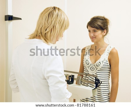 Woman doctor weighing the patient in clinic