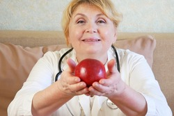 woman doctor with a red apple in his hand, depicting the idea of healthy food for a good health, closeup
