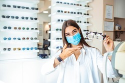 Woman doctor with protective face mask holds in his hands the optical test lenses for testing vision. Medical concept. Ophthalmologist holding try-on tool for lenses selection in the cabinet.