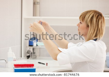 Woman doctor with test tube in laboratory