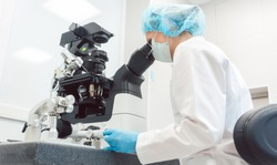 Woman doctor working in medical lab with manipulator and microscope