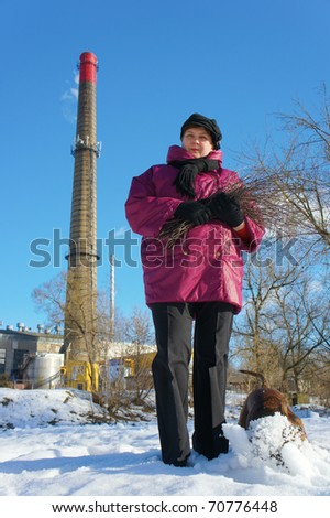 Woman, dog and  factory pipe of smoking against the sky