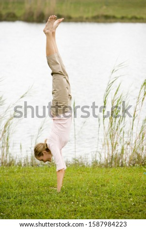 woman doing a handstand by the waterside