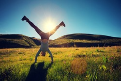 woman doing a handstand in a sunrise meadow