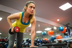 Woman doing a workout with dumbbells at the gym