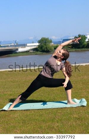 Woman doing a yoga side stretch in a green space outside the city