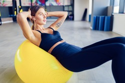 Woman doing abdominal crunches pilates exercise on exercise fitness ball at gym. Exercises for the abs. Swiss ball. Effort, dedication and motivation concept.