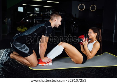 Woman doing abdominal crunches press exercise on the mat with her sports male trainer in gym concept sport, fitness, lifestyle and people. Couple exercises. Exercises with the ball #529107253