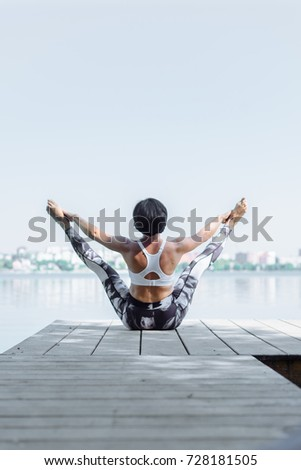 woman doing aerial fly yoga exercising outdoor #728181505