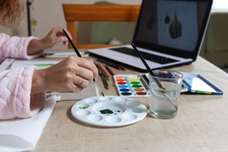 Woman doing an online course in watercolor painting, entertainment against the confinement of coranavirus
