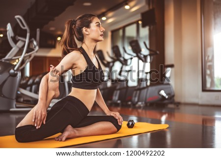 Woman doing bending legs yoga in fitness workouts training gym center background. Lifestyle woman sitting with sport dumbbell equipment and exercise treadmill background. Yoga girl in black sports bra #1200492202