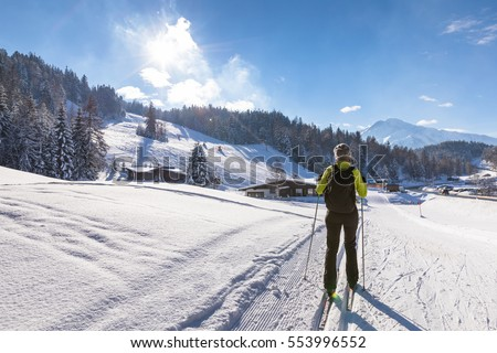 Woman doing cross-country skiing on groomed trail in snow-covered winter landscape with sunny weather and beautiful mountains in background #553996552