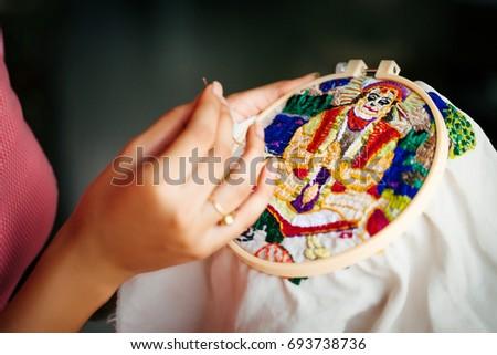 woman doing embroidery portrait of Hanuman - Indian god