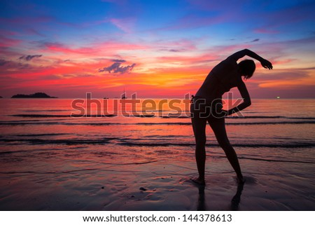 Woman doing exercise on the beach near the ocean at sunset in Thailand