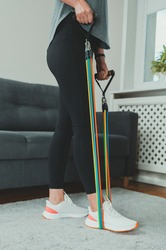 Woman doing exercises with resistance bands at home.