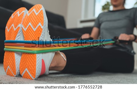 Woman doing exercises with resistance bands at home. Photo stock ©