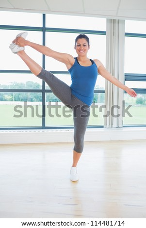 Woman doing extended hand to toe yoge pose in fitness studio