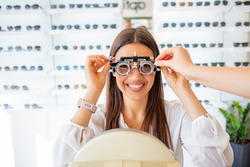 Woman doing eyesight measurement with trial frame and visual test chart on white. Ophthalmologist checking eyesight. Beautiful woman checking her sight at ophthalmologist with Eye Test Equipment.